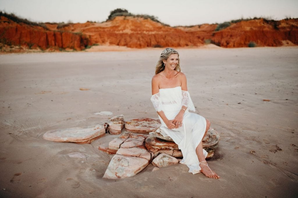 Broome bride sits on a rock on Riddell Beach in beautiful white wedding dress