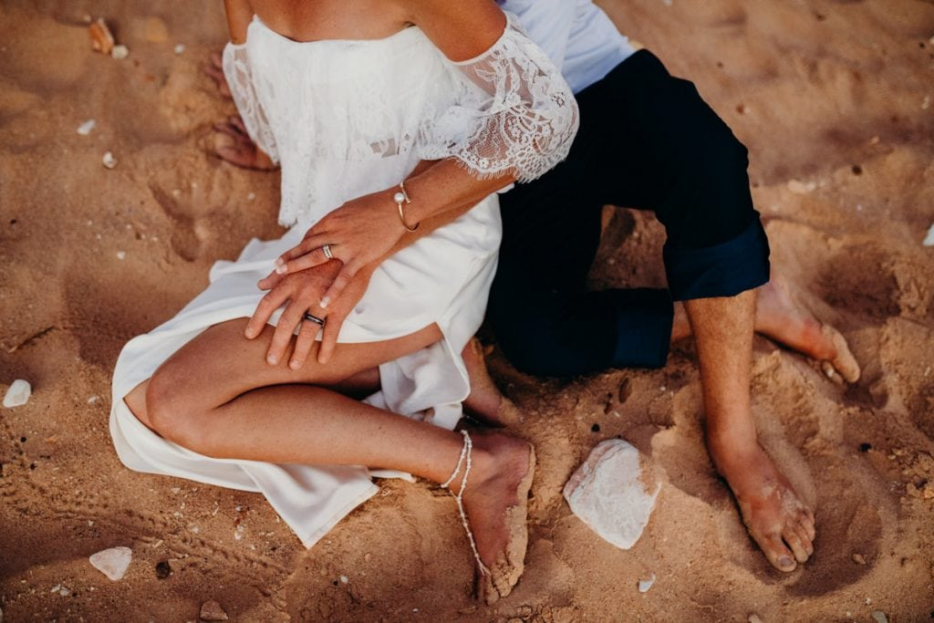 wedding couple sitting in the sand on the beach and holding hands
