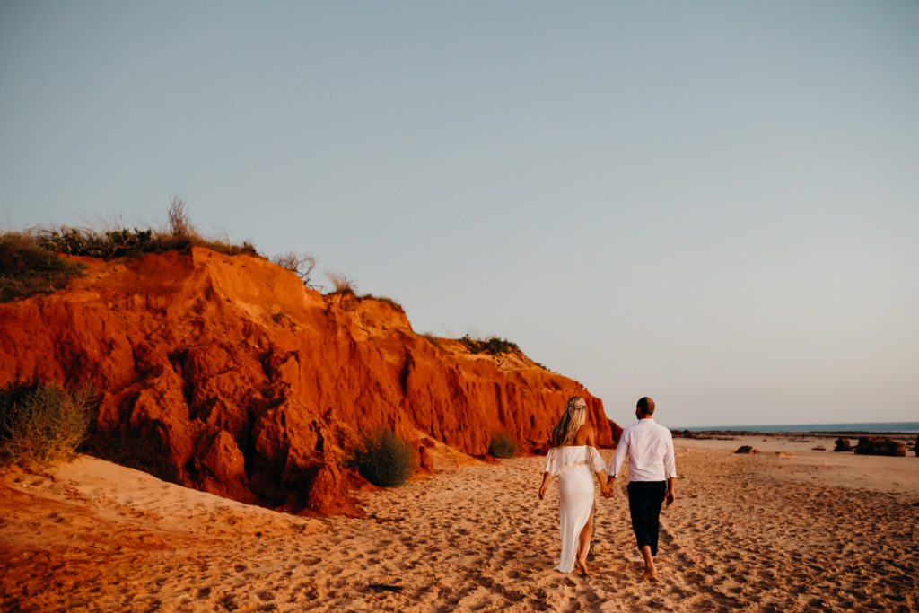 wedding couple walks hand in hand along Riddell Beach with red cliffs and Indian Ocean