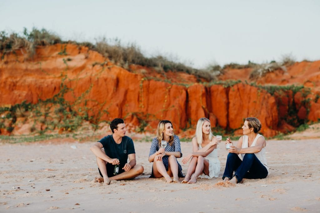 wedding guests drinking champagne and watching sunset on the beach in Broome