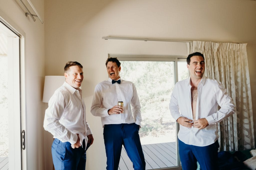 groom with two groomsmen laughing and drinking beer