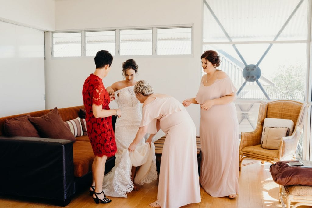 bride is getting help by bridesmaids and mother with getting into her wedding dress