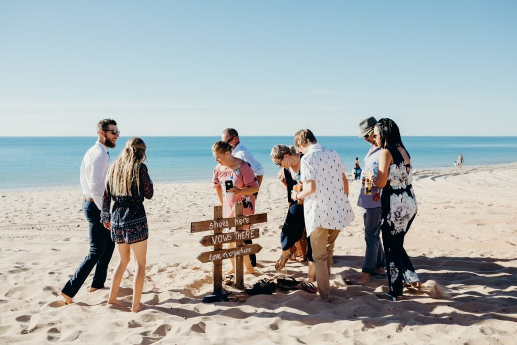 wedding guests leaving shoes at wooden sign on the beach