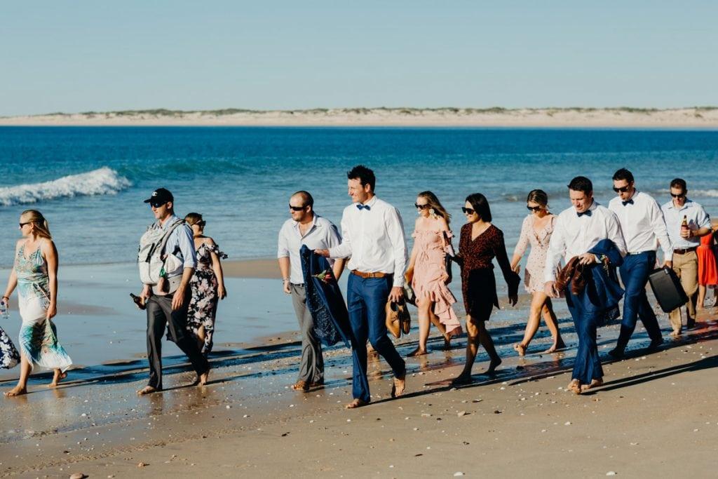 groom and wedding guests walking on Eco Beach
