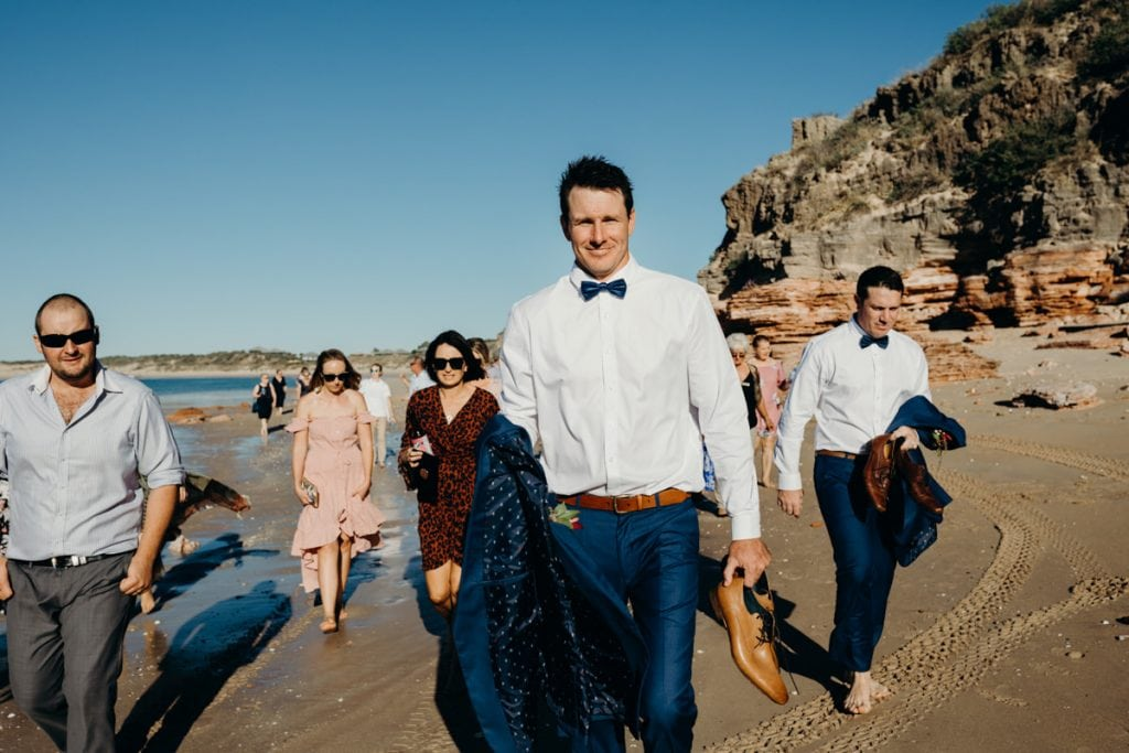 Groom with his shoes in his hands walking to ceremony location