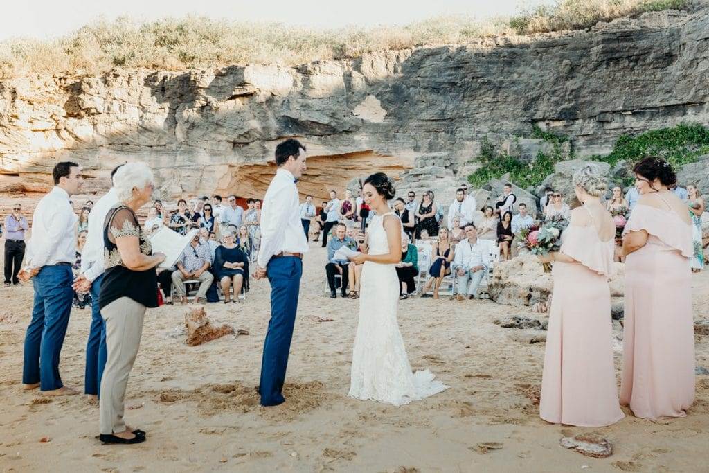 wedding ceremony on the beach with cliffs in the background