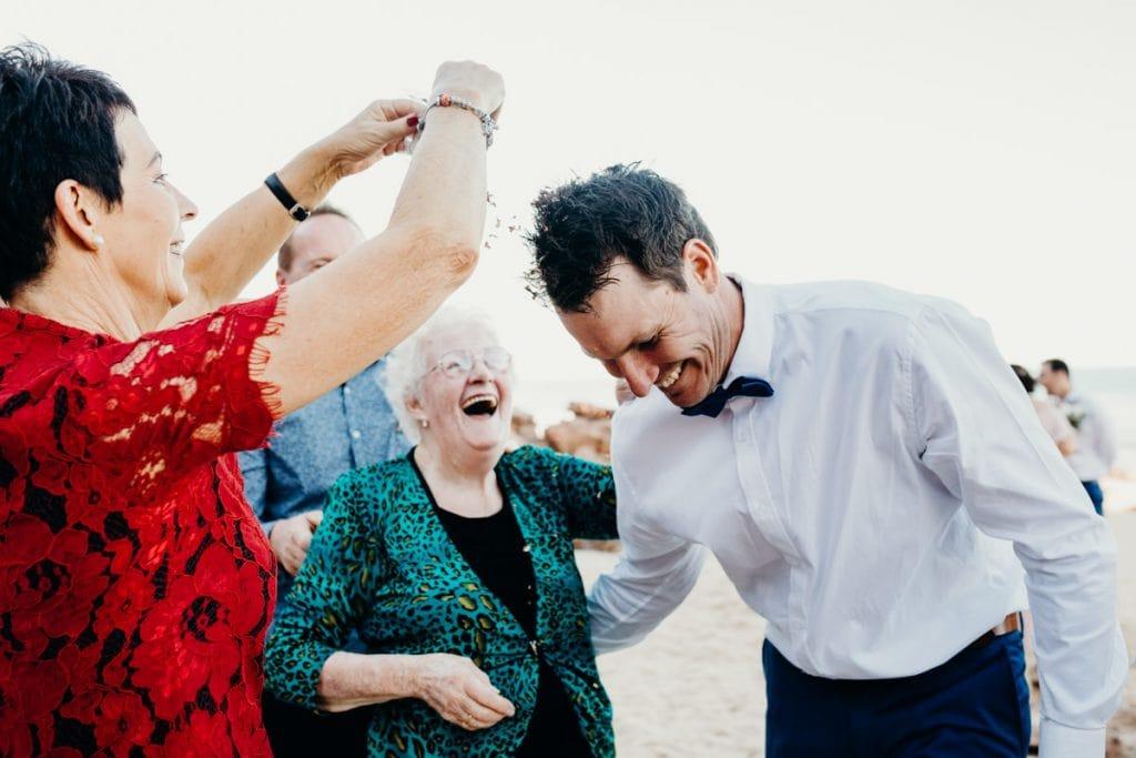 grandma and mother-in-law sprinkle flower petals on groom's head