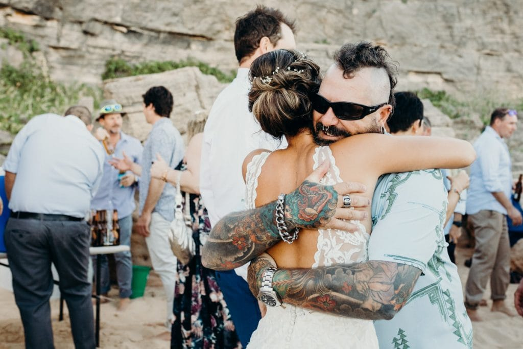 wedding guest with tattoos hugs bride