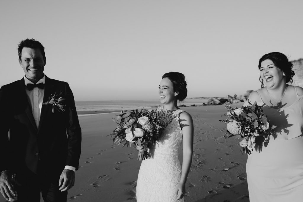 laughing bride on the beach with flower boquet