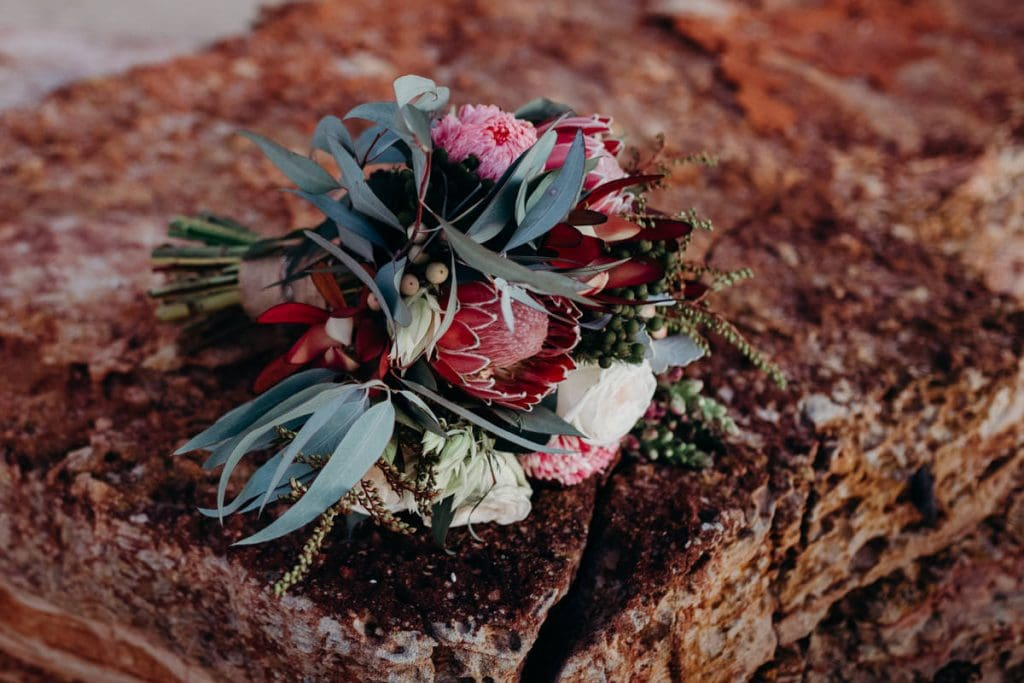native flower bouquet by Broome Florist lying on a rock on Eco Beach