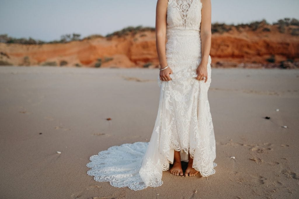 barefoot bride standing on the beach