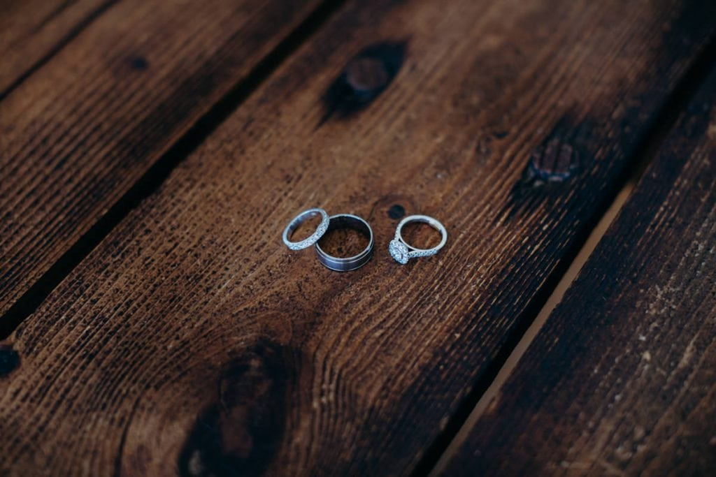 wedding ring and engagement ring on wooden surface
