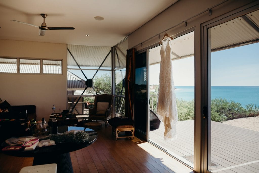 wedding dress hanging up on the hotel room glass door with Eco Beach in the background