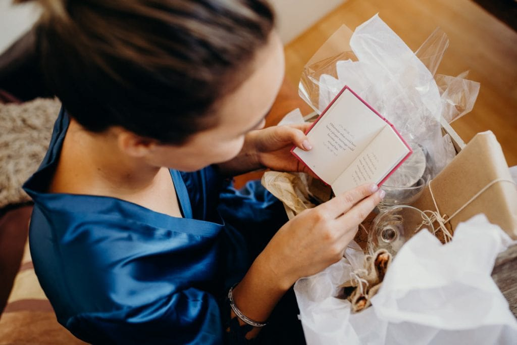 bride in blue robe with gift of her sister on her wedding day