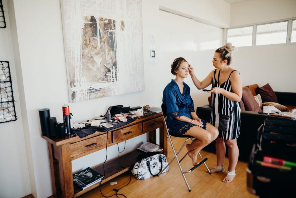 makeup artist applying makeup to bride in Eco Beach Resort bungalow