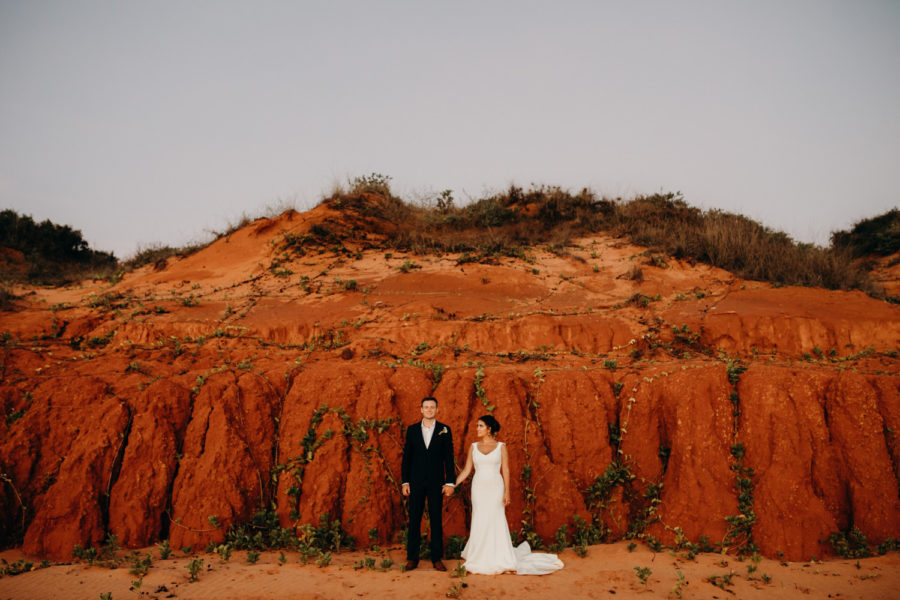 Bride and groom in front of cliff in Broome