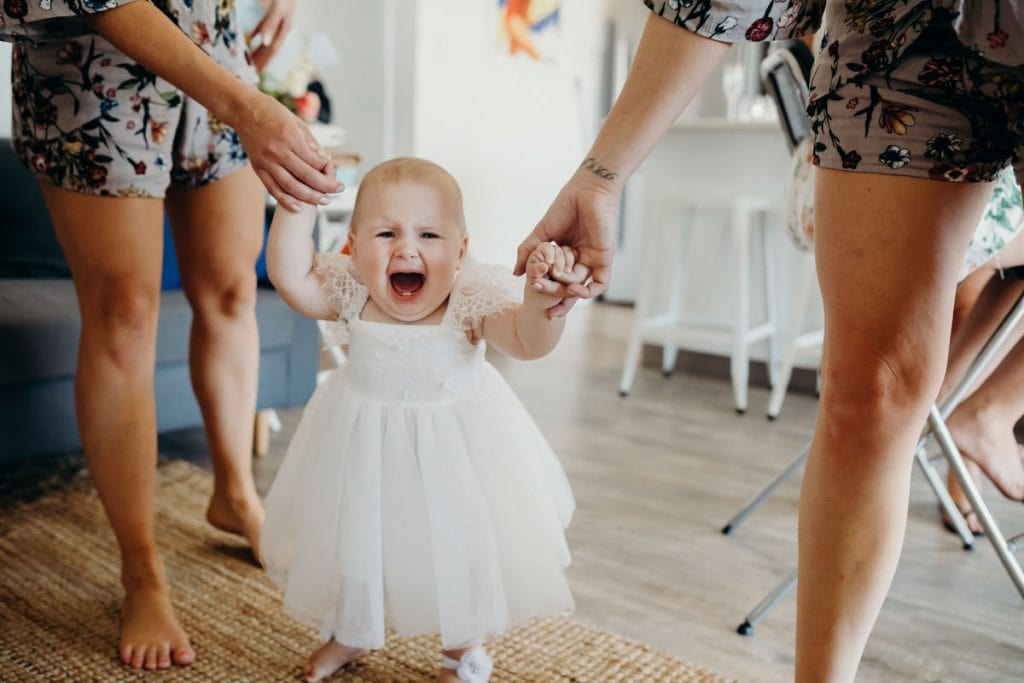 crying baby in white dress walking towards the bride