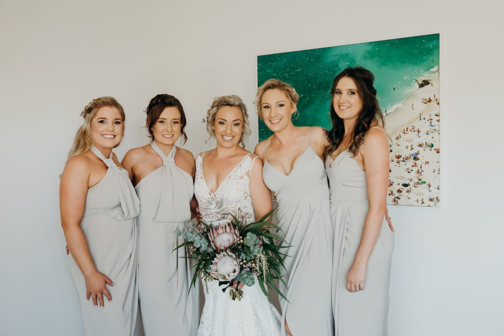 group photo of bride and her bridesmaids at hotel room
