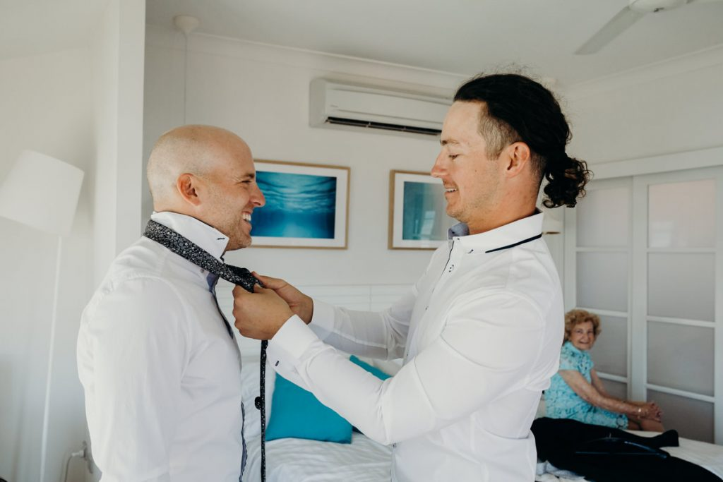 best man is tying tie around groom's neck at Mangrove Hotel in Broome