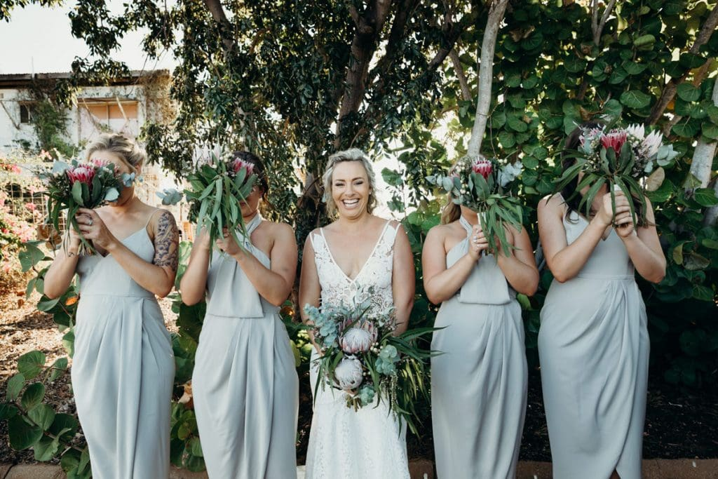 bride and bridesmaids standing in line with Broome Florist flower boquets