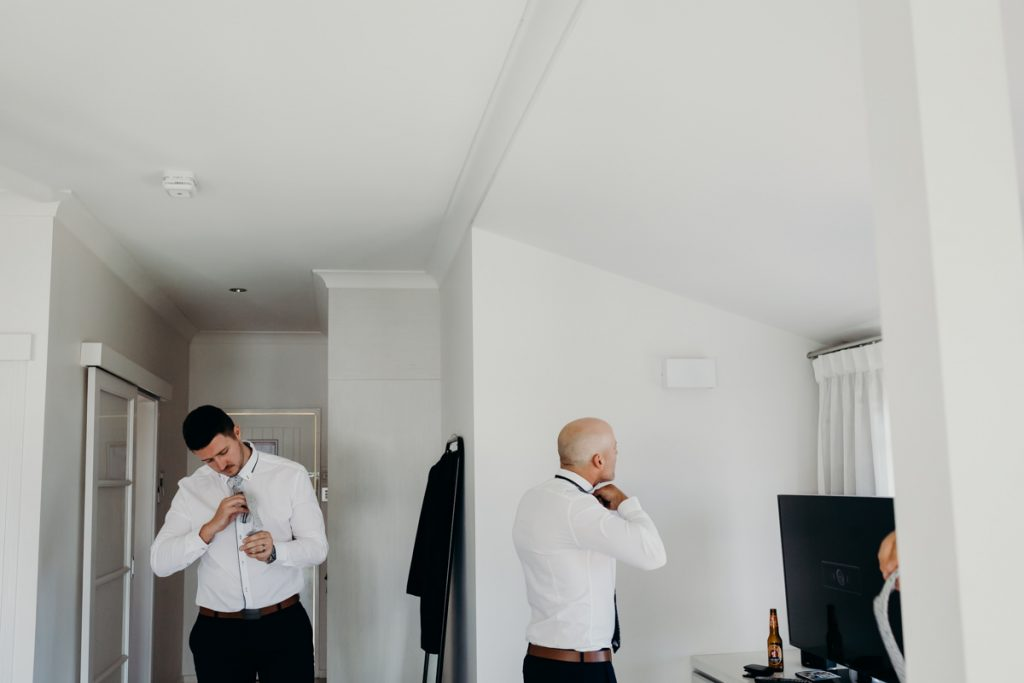 groom and groomsman getting ready at Mangrove Hotel room