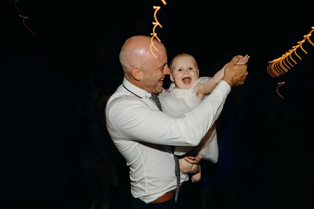 man is dancing with baby on Broome dancefloor