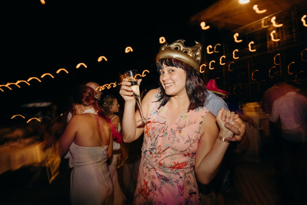 wedding guest on dance floor with glass of champagne in her hand