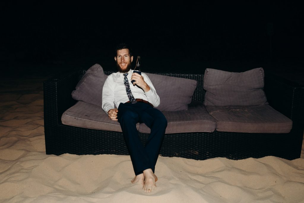 wedding guests sits on couch on the beach with beer in his hand