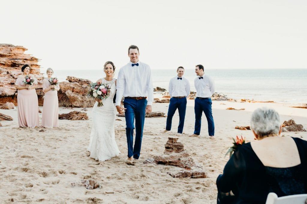 married couple walks down the sandy aisle on the beach