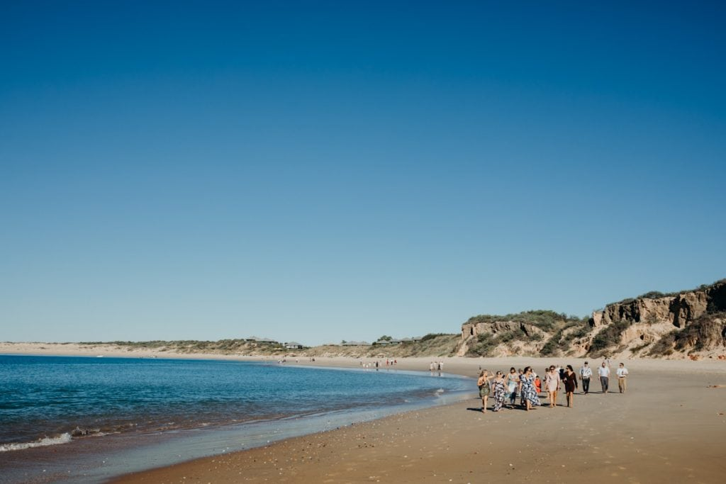 wedding guests walking along Eco Beach to ceremony location