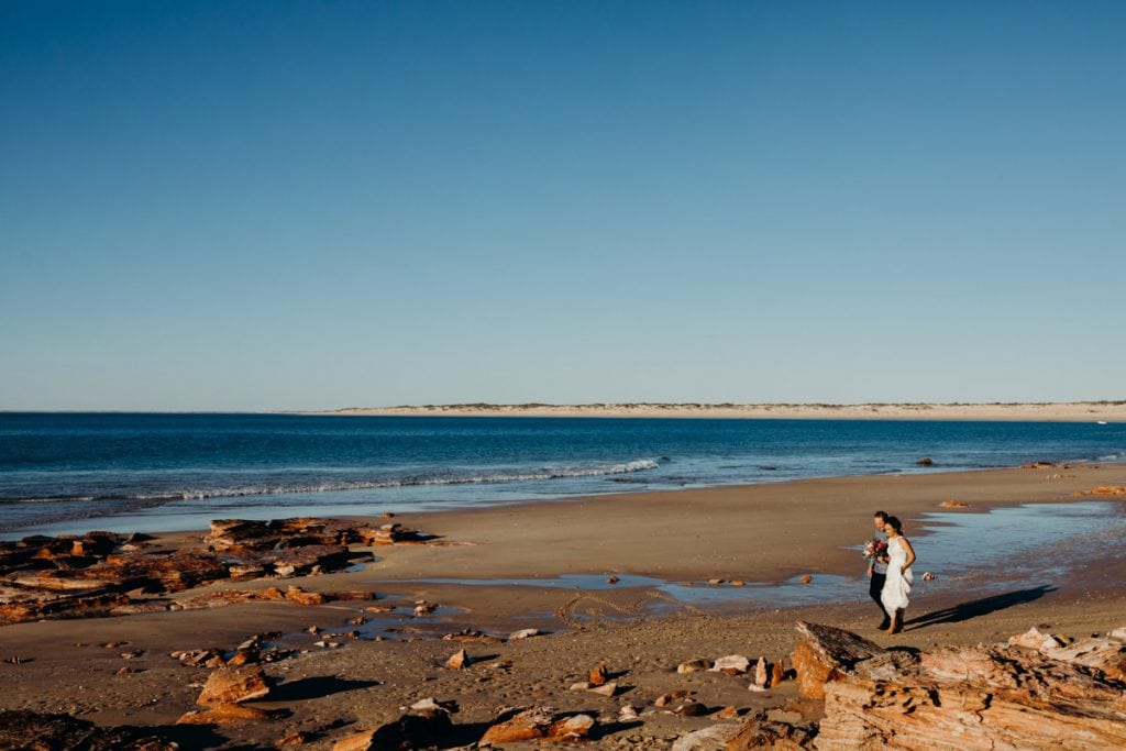 bride with father walking on Eco Beach to wedding ceremony