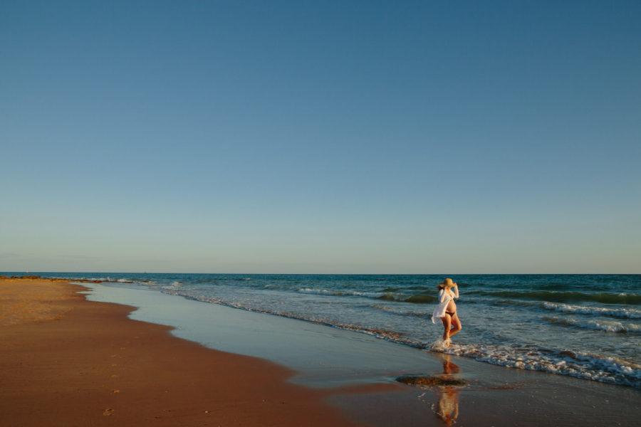 pregnant woman wearing hat walking on beach