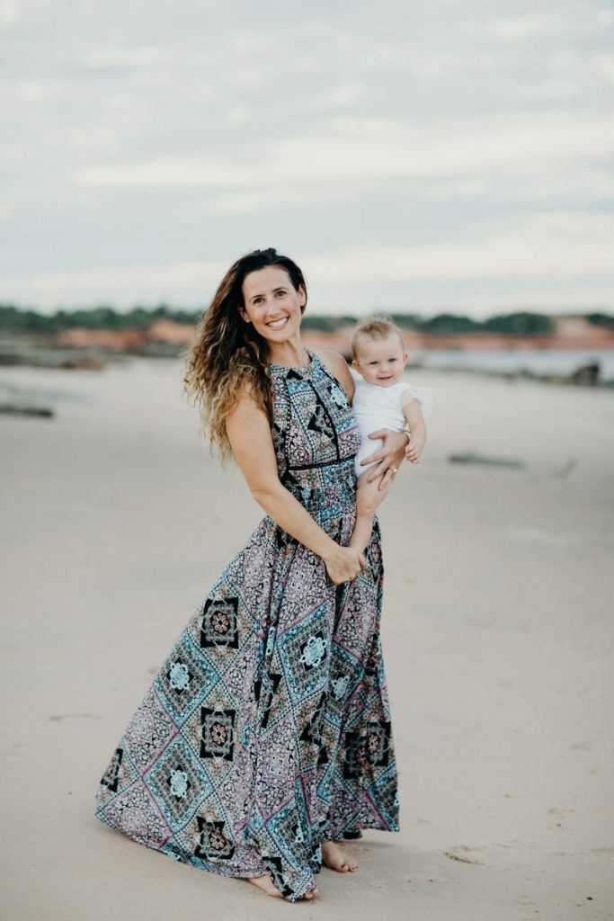 woman in dress on beach with baby in her arms