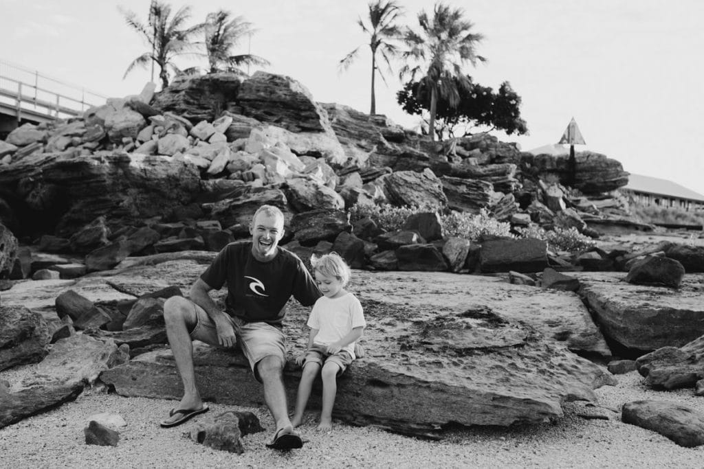 father and son sitting on the rocks at Broome Port
