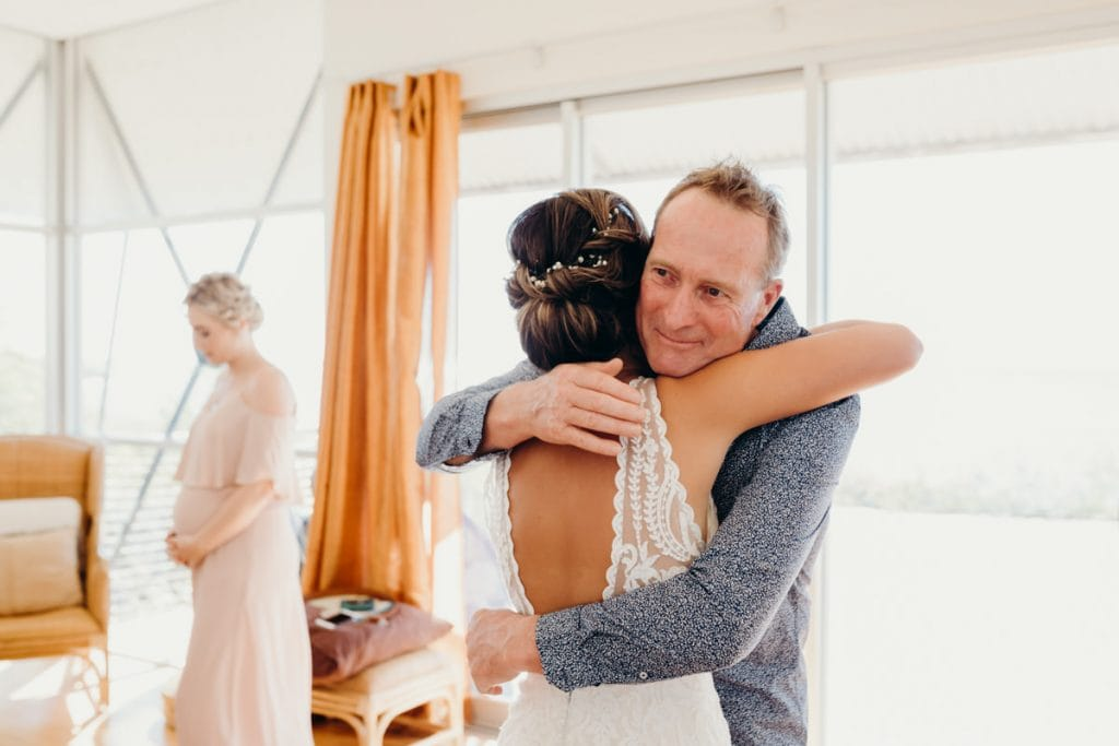 father of the bride gives his daughter a hug after seeing her in her wedding dress for the first time