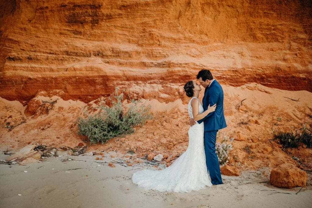 wedding couple standing in front of red pindan cliff