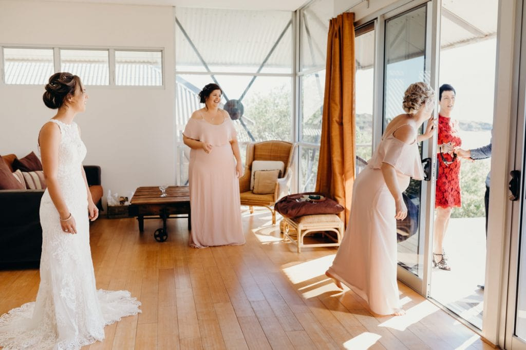 father of the bride enters Eco Beach villa to see his daughter in wedding dress