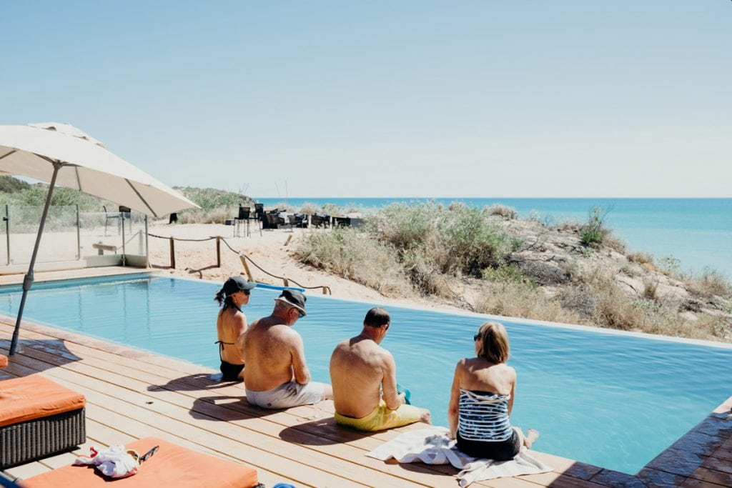 wedding guests sitting at swimming pool with ocean view