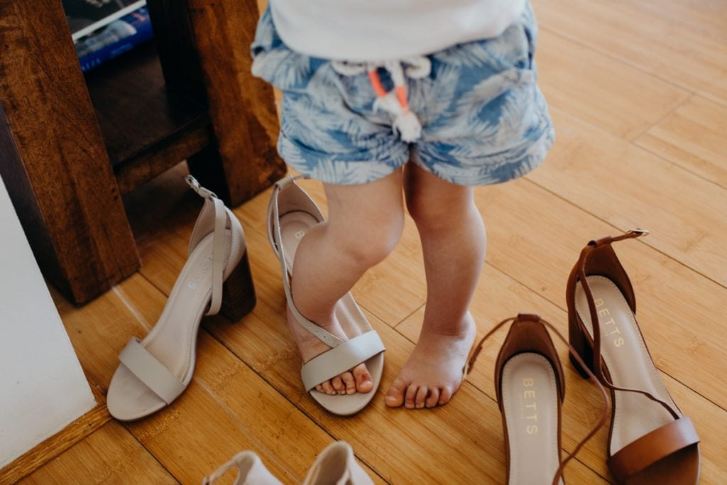 feet of little girl trying on wedding shoes