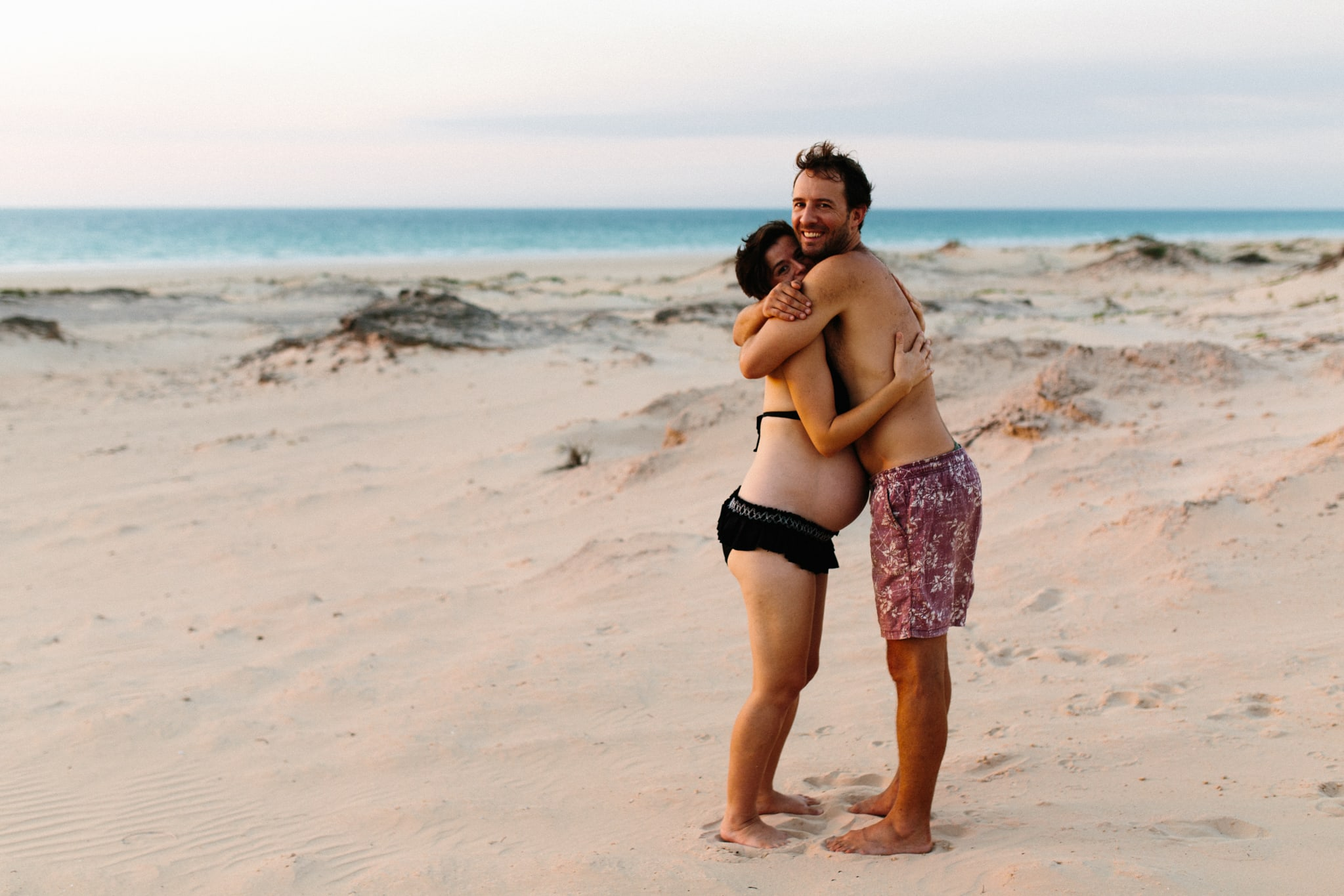 smiling man hugs his pregnant wife in Cable Beach dunes