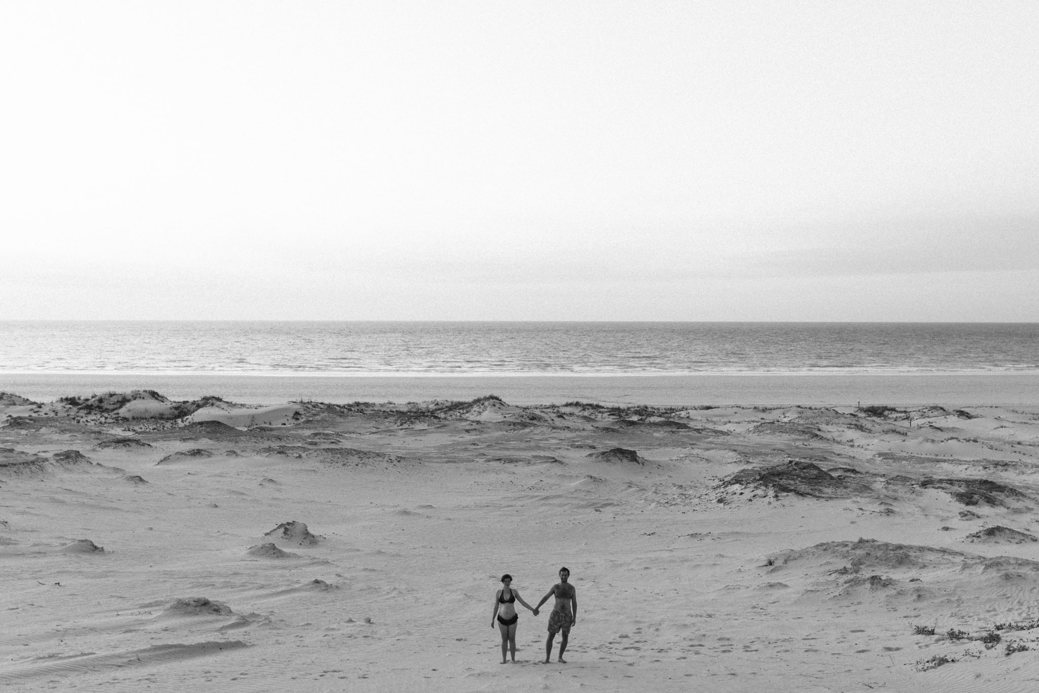 black and white shot of couple holding hands with ocean in the background