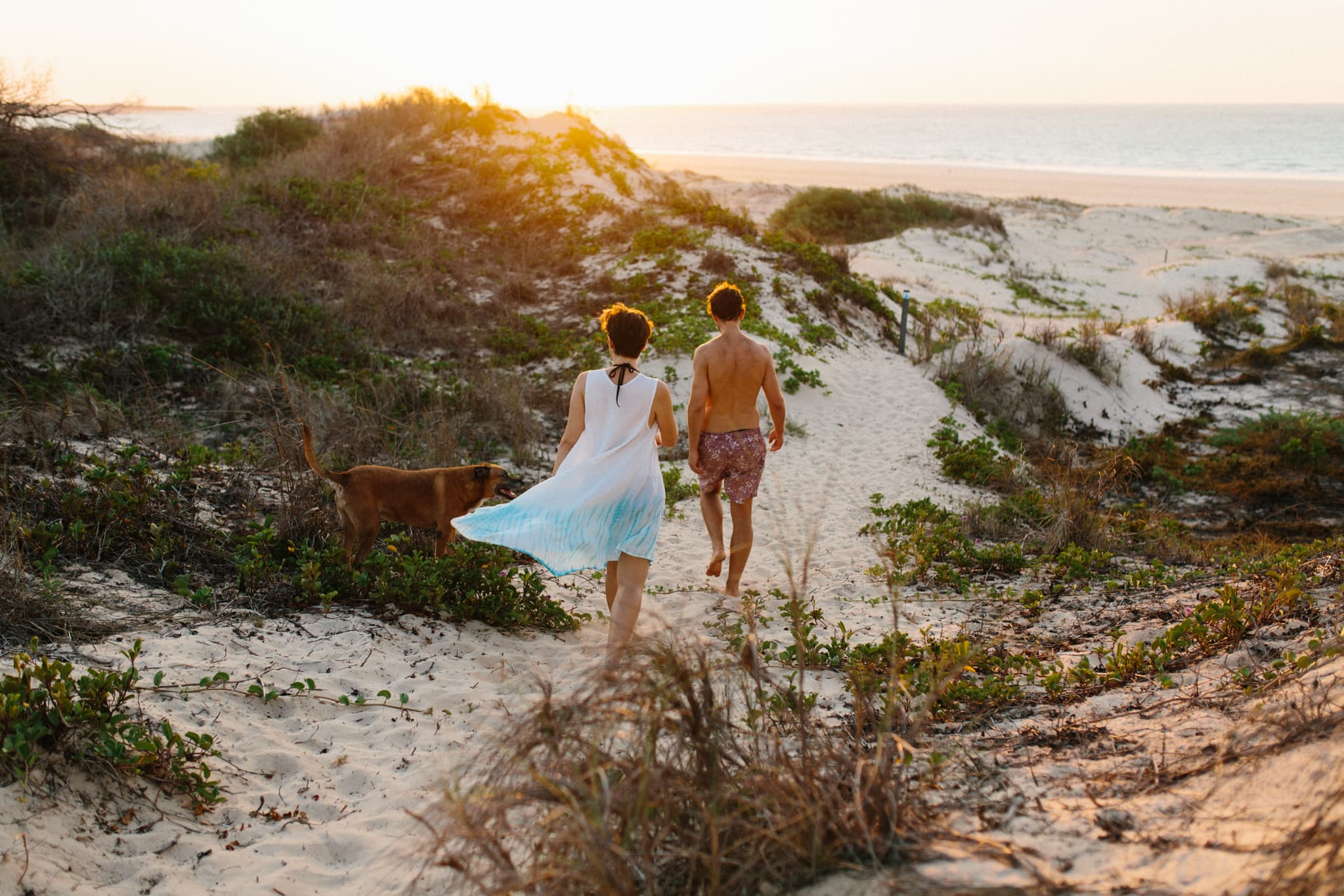 Maternity couple walking through the dunes towards the water during