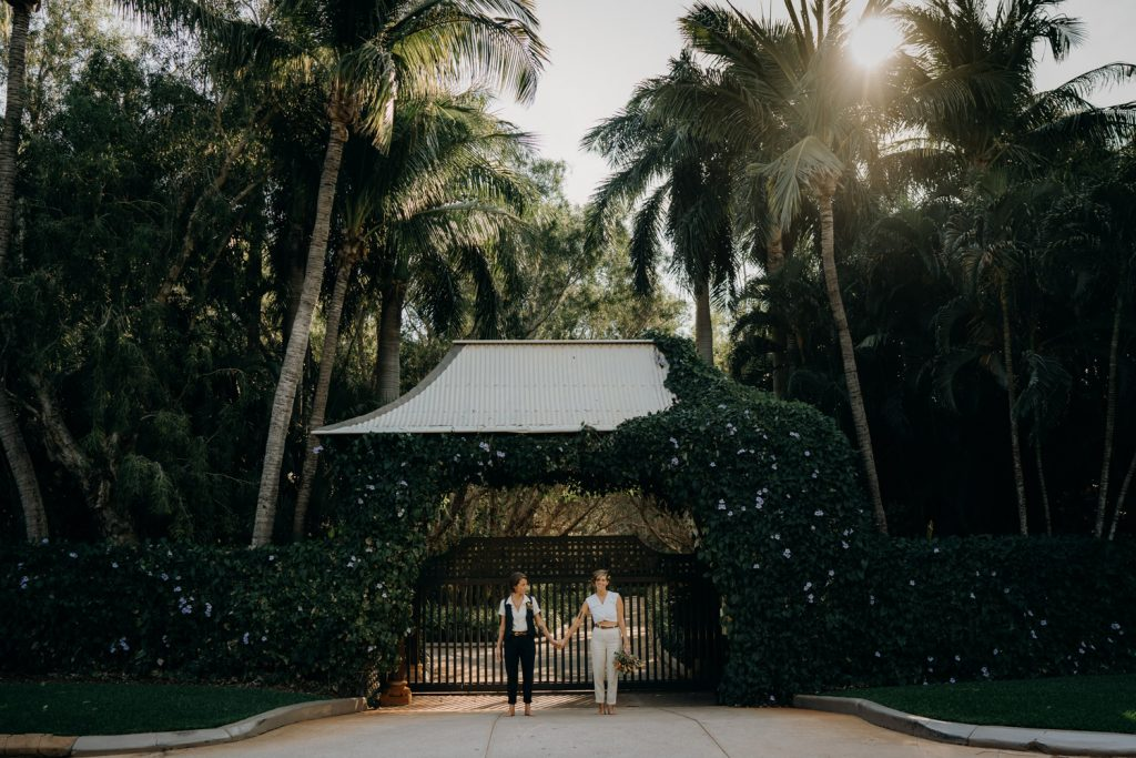 Broome elopement couple stands in front of large gate with palm trees