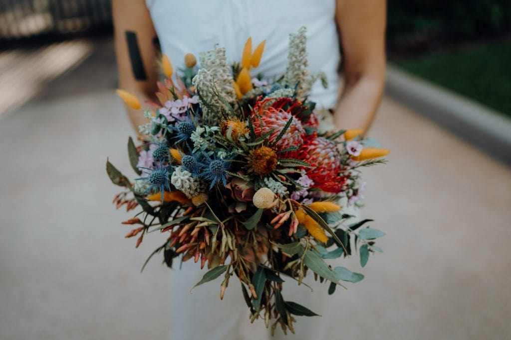 bride holding up a very colourful flower bouquet