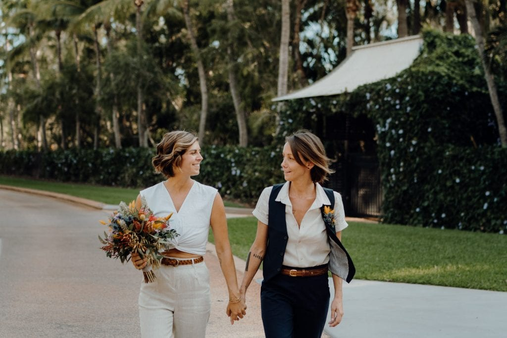 young same-sex couple walking along the streets of Broome in Western Australia with palms in the background