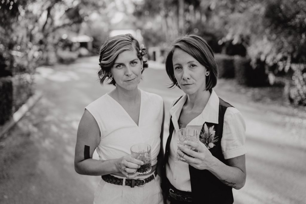 two women in dress clothes and with drinks in their hands standing in parking lot on their wedding day