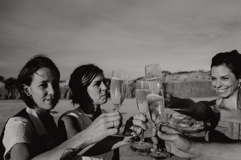 wedding couple and their celebrant toasting with champagne at their Broome elopement