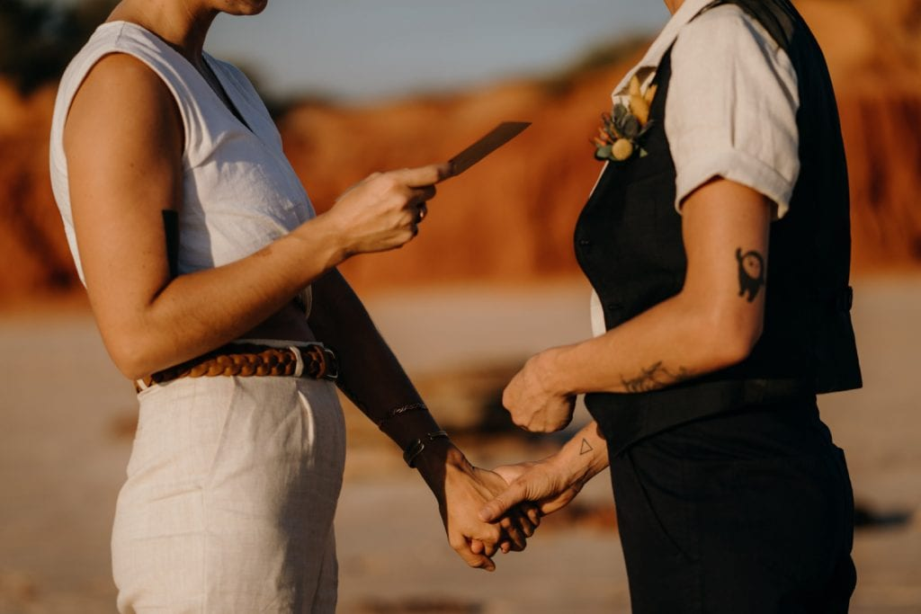 two people holding hands during Broome elopement wedding with tattoos on their arms