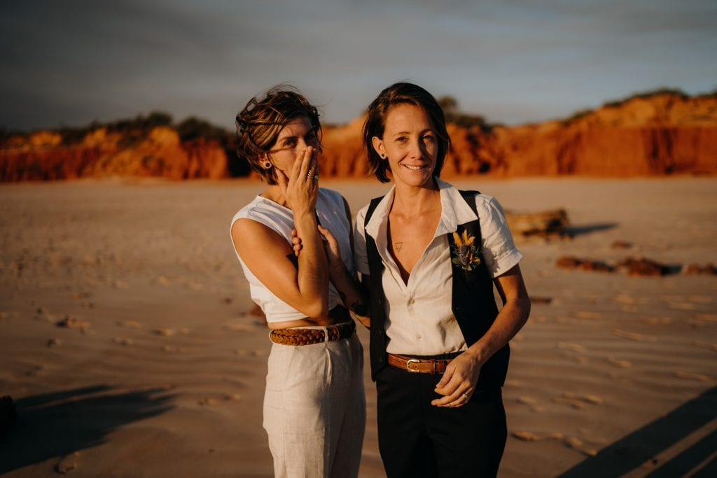 emotional bride with her wife at Broome beach with red cliffs