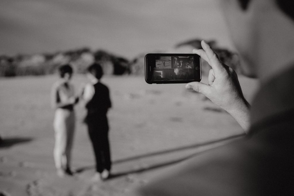 mobile phone screen showing zoom wedding with brides sharing vows in background